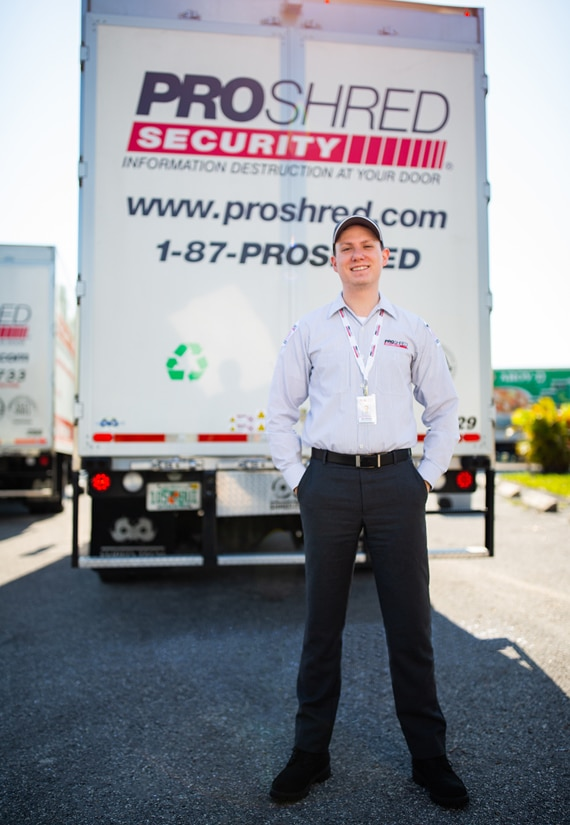 PROSHRED employee standing behind a mobile shredding truck.