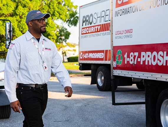 PROSHRED employee walking beside a shredding truck in a residential area.