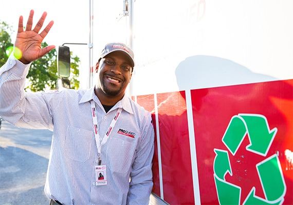 PROSHRED employee waving in front of a mobile shred truck with a recycling emblem.